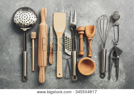 Flat Lay Kitchen Tools And Utensils On A Gray Concrete Background, Toned. Top View. Kitchenware Is M