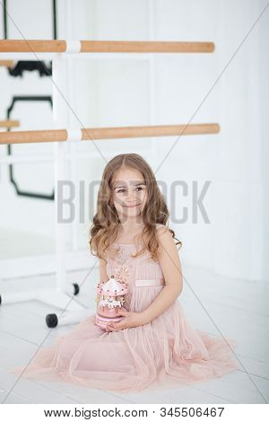 Cute Little Girl Dreams Of Becoming A Ballerina. Little Ballerina In Dress Sits In A Dance Class On