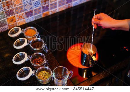 Mulled Wine Preparation, A Metal Kettle Stands On The Stove, The Hand Stirs, Next To The Table Are T