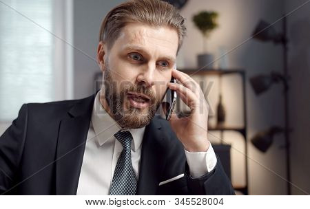 Portrait Of Vigorous Bearded Adult Businessman In Formal Suit Talking On Phone In Office