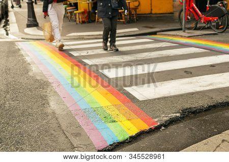 Paris, France 2019. Gay Pride Flag, Rainbow Flag Of The Lgbt Community On Crosswalk With People Cros