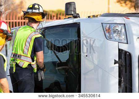 Emergency Responders Cracking The Window Of A Mini Van At Accident Site