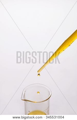 Dropping Sesame Oil From A Plastic Pipette Into A Glass Beaker, A Segment Of A Beaker, Motion Of Dro