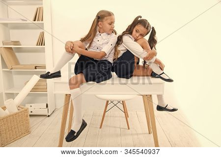 A Boring Lesson. Cute School Children Sitting At Table. Little Schoolgirls Got Tired Of Lesson In Pr