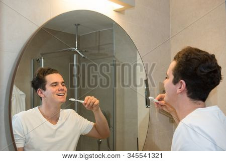 young caucasian man brushing teeth looking at mirror reflection in bathroom morning clean