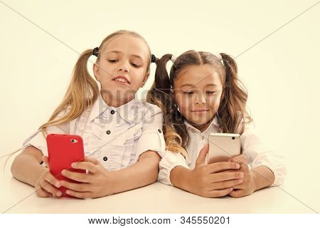 Modern Students. Small Students Using Mobile Phones In Classroom Isolated On White. Little Students