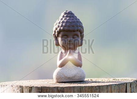 Morning Meditation. Little Buddha Or Monk Figurine Doing Yoga Exercises