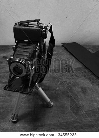 Medium Format Folding Camera With Tripod On A Table