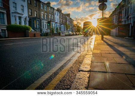 London, England - August 17 2019; Looking Into Sun Burst Along Graham Road As Bus Approaches In Hazy