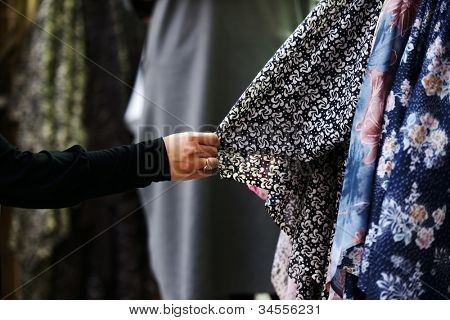Woman choosing clothes at market poster