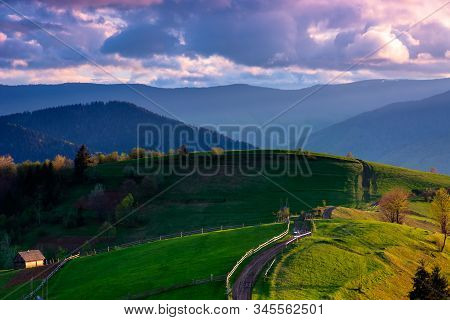 Mountainous Rural Landscape In Evening Light. Wooden Fence Along The Path Through Rolling Hills In F