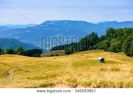 Mountainous Countryside In Summertime. Country Road Down The Hill Through The Grassy Meadow. Woodshe