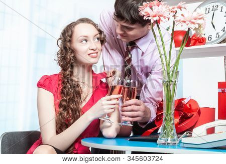 A Young Man, An Employee Of The Company Shows Courtship To His Colleague-a Young Woman With Curly Ha