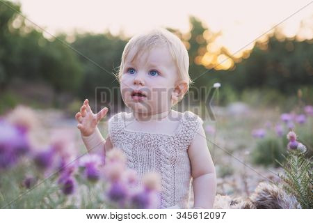 A Cute Little Baby With Big Blue Eyes In Nature In Flowers Looks At The Camera In The Spring. Concep