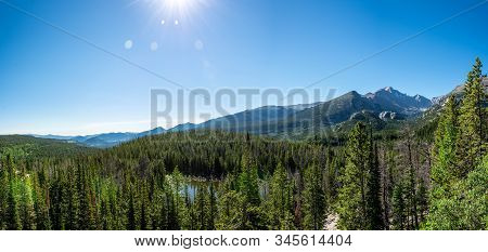 Breathtaking Panorama Over The Forest With Mountain Range In The Background On A Sunny Day With Blue