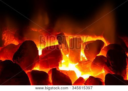 Red Hot Coal Bars In Focus On Dark Background With Flames. Background Of Raw Coal With Soft Focus Ex