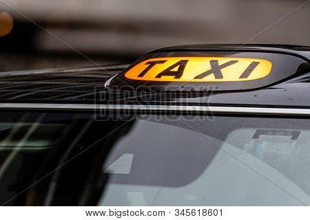 A British London Black Taxi Cab Sign With Defocused  Background - Image