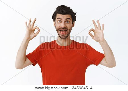 Enthusiastic Good-looking Bearded Man In Red T-shirt, Showing Alright, Okay Or Ok Sign And Smiling P