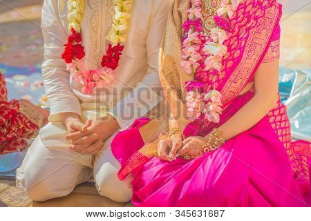 The Caucasian Bride And Groom In Saree With Flower Garlands Sit On The Floor At An Indian Wedding Ce