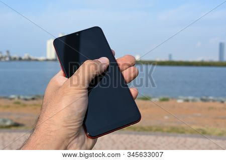 Mobile Or Cellular Smart Phone Outdoors With Male Caucasian Hand Holding Or Gripping Phone. Telecomm