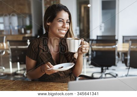 Woman Enjoys Tasty Coffee In Cafe During Lunch. Attractive Female Entrepreneur Working Remote At Co-