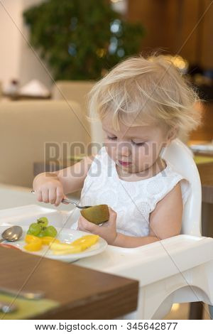 little caucasian girl eating fruits indoors at home healthy eating