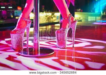 Young Sexy Woman Pole Dancing Striptease With Pylon In Night Club. Beautiful Stripper Girl On Stage.