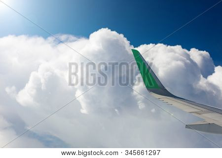 View From The Window Of An Airplane, White Clouds, Blue Sky, Wing Of An Airplane. Ray In The Upper L