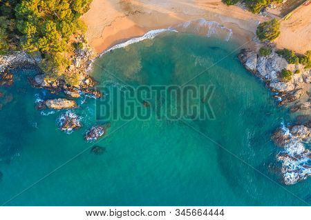Top View On Seashore With Turquoise Water And Sandy Beach. Rocks And Sand At The Seashore.