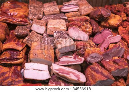Smoked Meat Delicacies And Sausages On The Market Balyk Of Various Meats In A Shop Window. Deli Disp