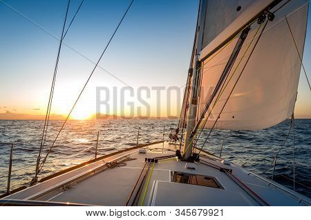 Chasing The Sun At Sailing Yacht. Deck And Sails Of Sailoat Pointing To The Sunrise. Mediterranean S