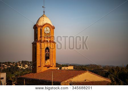 View Of A Bell Tower Illuminated By The Sunset Orange Light With Blue Sky In The Background