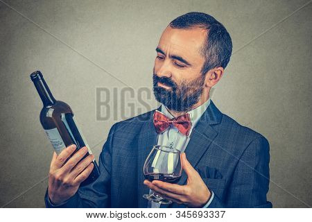 A Man With A Glass Of Wine Holding, Looking At A A Bottle, Reading The Information On It. Mixed Race