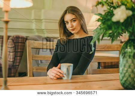 Beautiful Elegant Brunette Girl Wearing A Black Dress Is Relaxing In A Street Cafe. Advertising, Fas