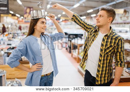 Couple jokes with ladle and pan in houseware store