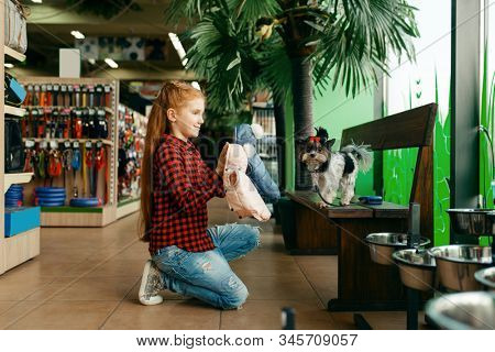 Little girl looking clothes for dog in pet store
