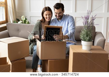 Happy Couple Unpack Boxes Settling At New Home