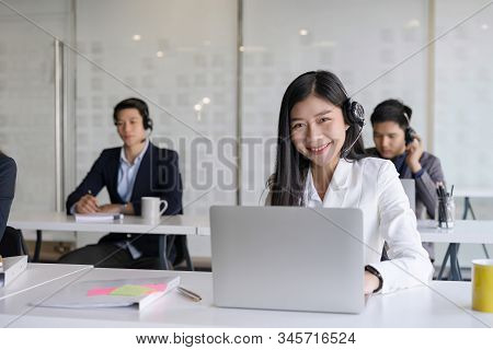 Attractive Young Asian Male Call Center Agent In Headset Consulting Client. Customer Service Team Su