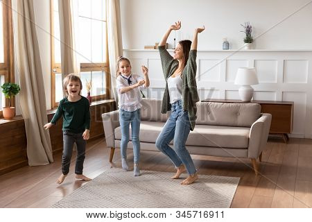 Overjoyed Mum Have Fun Dance With Little Kids At Home
