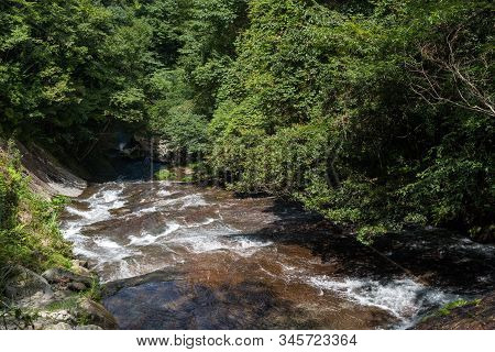 Sharrow River Flowing Down On A Bedrock Slope Under Green Forest