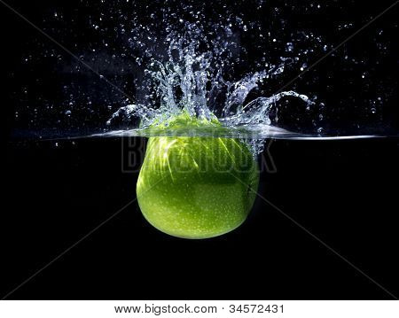 Green granny smith apple, splashing in water