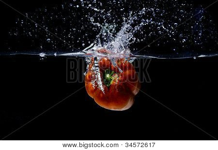 Fresh sweet red pepper, splashing in water