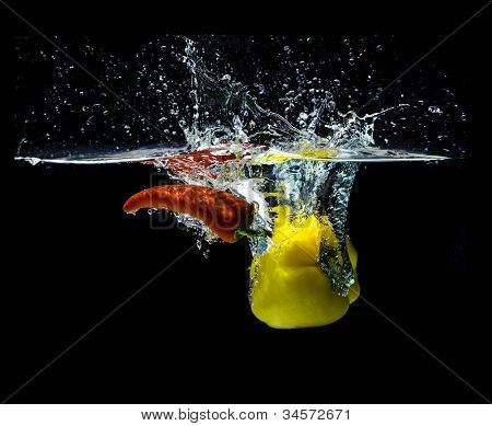 Red fresno and sweet yellow peppers, splashing in water