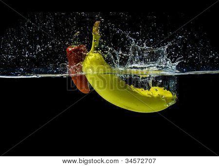 Red fresno pepper and yellow banana splashing in water
