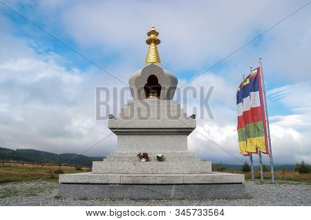Granite Stupa Of Enlightenment And Buddhist Flags Against Cloud Sky Background. Buddha Statue Inside