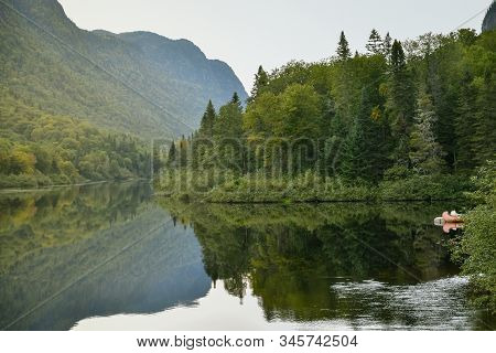 River Across The Forest In Jacques-cartier National Park, Canada In A Foggy Moody Sunset.