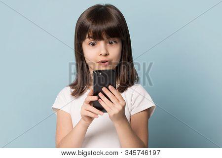 Headshot Studio Portrait Astonished Kid Girl Looking At Smartphone Screen.