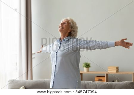 Happy Smiling Older Woman Standing With Arms Outstretched At Home