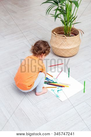 Curly Girl Plays With Colored Pencils  On The  Floor At Home. Vertcal Photo