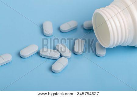 Blue Pills And White Plastic Medicine Bottle On Blue Background